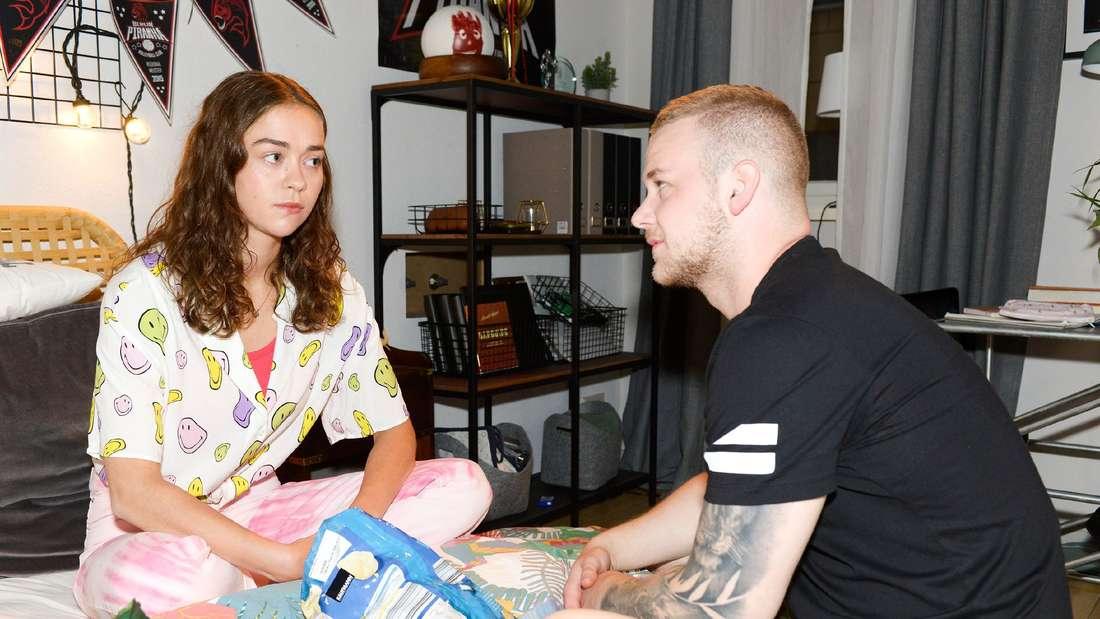 GZSZ: Merle und Jonas sprechen und sitzen auf einem Bett.