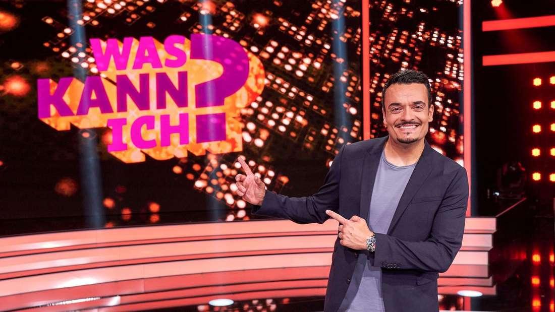 """Giovanni Zarrella auf der TV-Show-Bühne mit dem """"Was kann ich?""""-Logo im Hintergrund"""