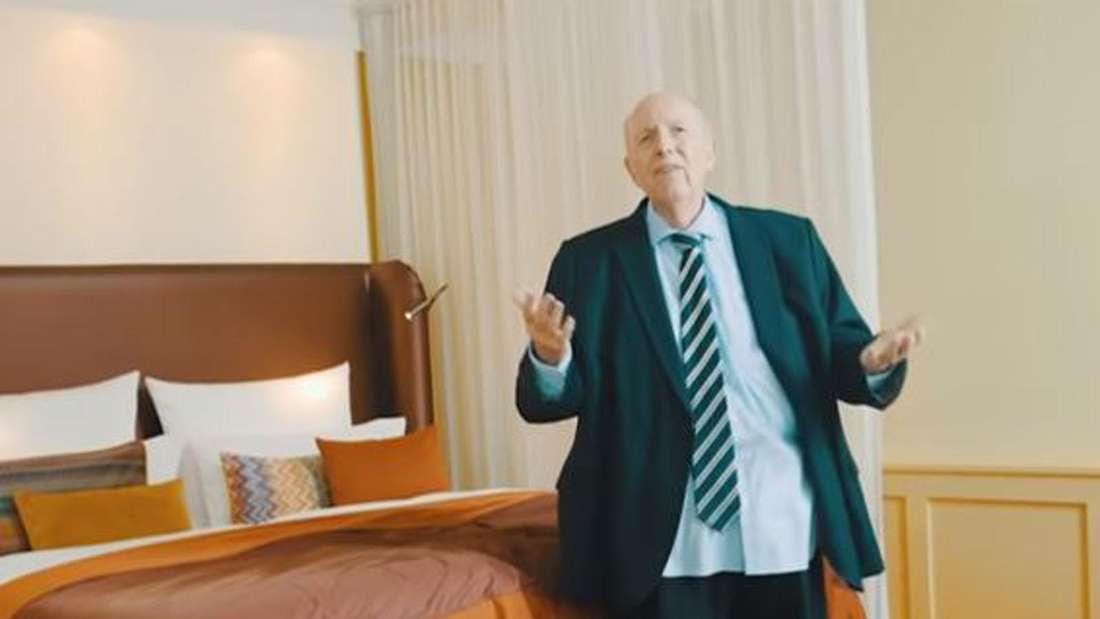 Reiner Calmund steht ohne Hose in Boxershorts in einem Hotelzimmer