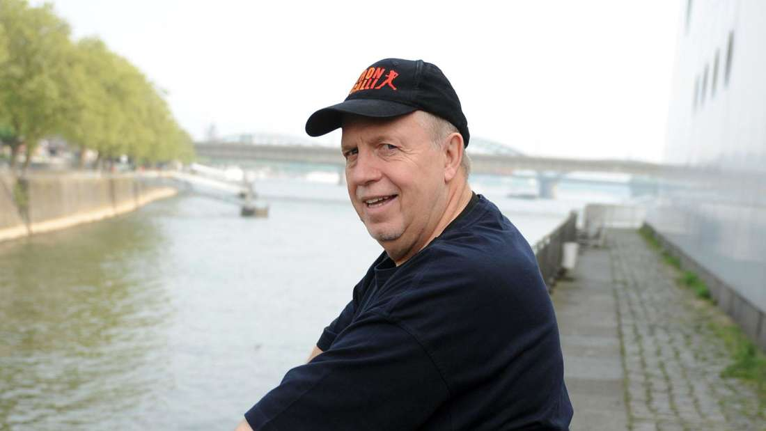 Reiner Calmund steht am Rhein-Ufer und macht sportliche Übungen