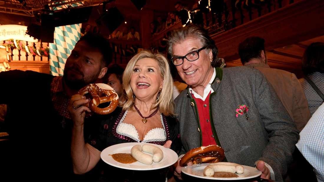 Marianne und Michael auf dem Oktoberfest mit Wurst und Brezen auf dem Teller