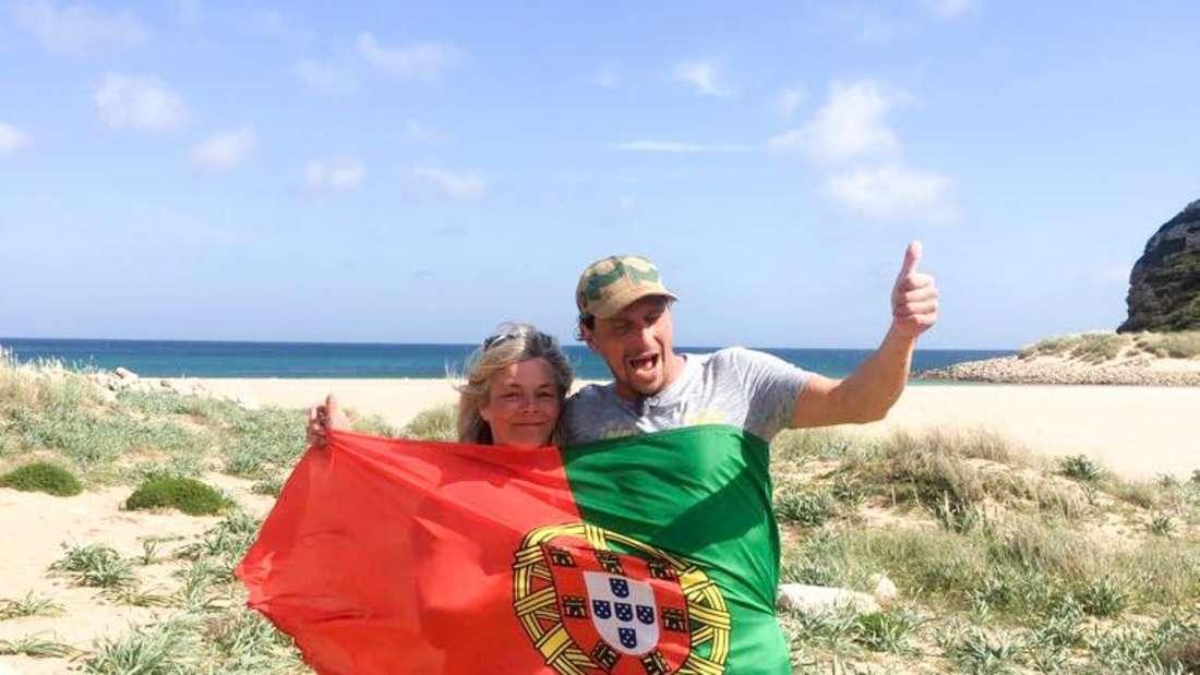 Kathi und Stephan halten eine Portugal-Flagge hoch.