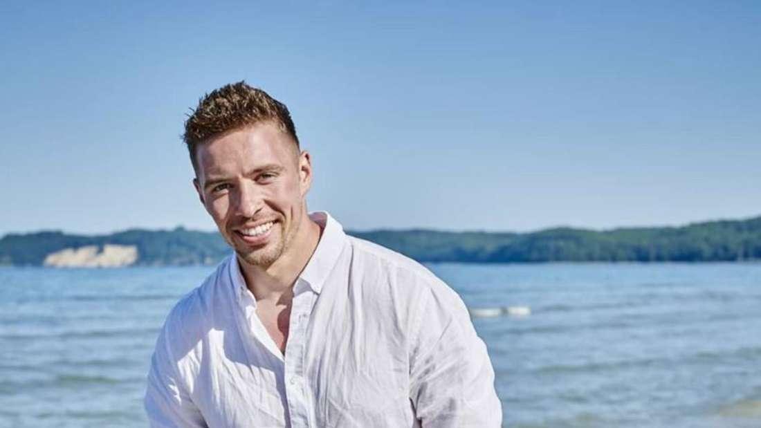Ramon Roselly geht am Strand spazieren und lacht in die Kamera