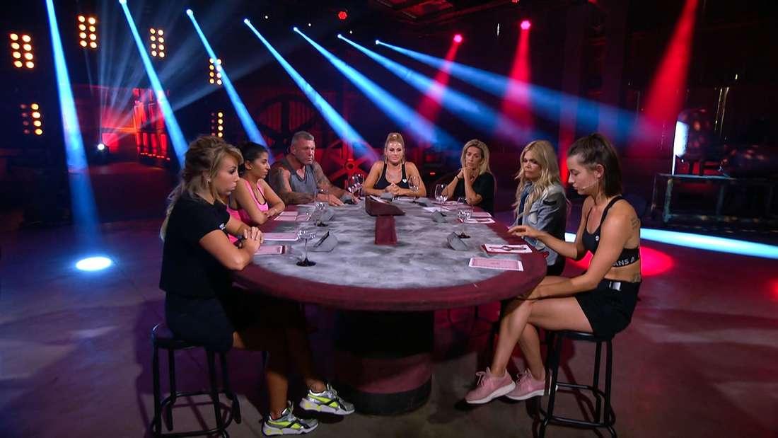 """Alle """"Sommerhaus der Stars""""-Kandidaten sitzen an einem Tisch - vor ihnen stehen Weingläser"""