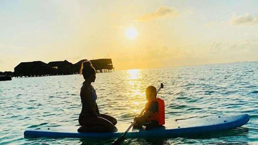 Sarah Lombardi und ihr Sohn sitzen auf einem Stand-Up-Paddle auf dem Meer und schauen in den Sonnenuntergang.