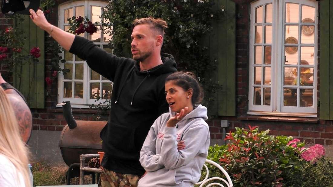Eva und Chris stehen draußen und winken Jenny und Andrej zu.