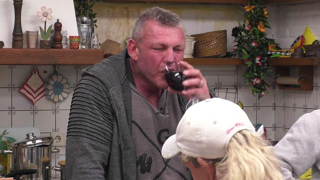 Andreas Robens trinkt im Sommerhaus der Stars einen Schluck Rotwein.