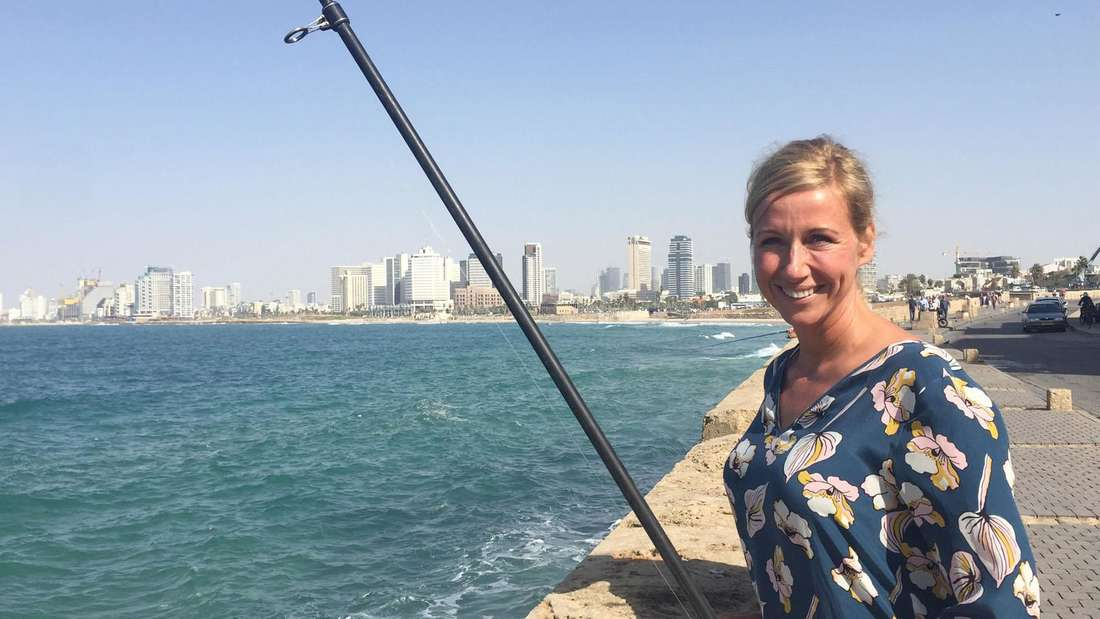 Andrea Kiewel in Tel-Aviv auf einer Brücke. Die Moderatorin lacht in die Kamera