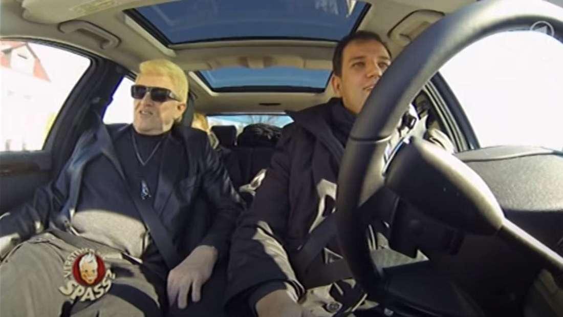 Schlagersänger Heino sitzt mit seinem Manager im Auto. Sie nehmen zwei Anhalter mit.