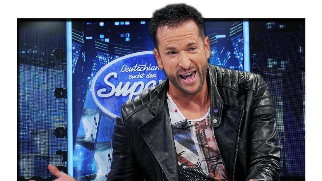 """Michael Wendler lächelt in der Auftaktsendung der SAT.1 Fernsehshow """"Promi Big Brother - Das Experiment"""" am 15.08.2014. Im Hintergrund: Die DSDS-Bühne mit Logo (Fotomontage)"""