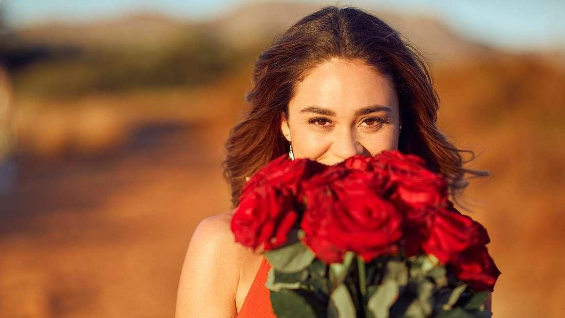 Melissa Damilia mit einem Strauß roter Rosen