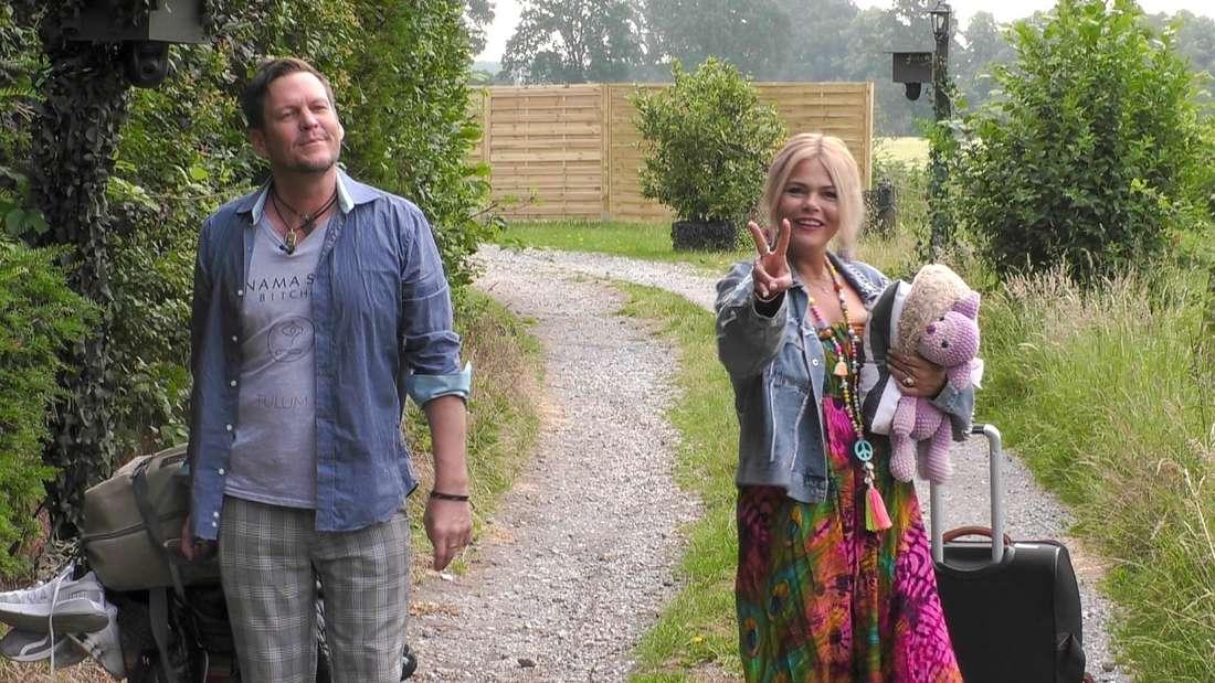 Diana und Michael haben einen Koffer in der Hand und gehen auf einem steinigen Weg.