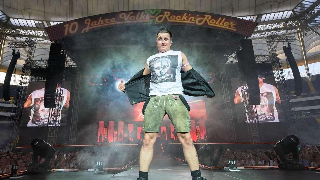 Andreas Gabalier steht auf der Bühne und zieht sich grade seine Jacke aus