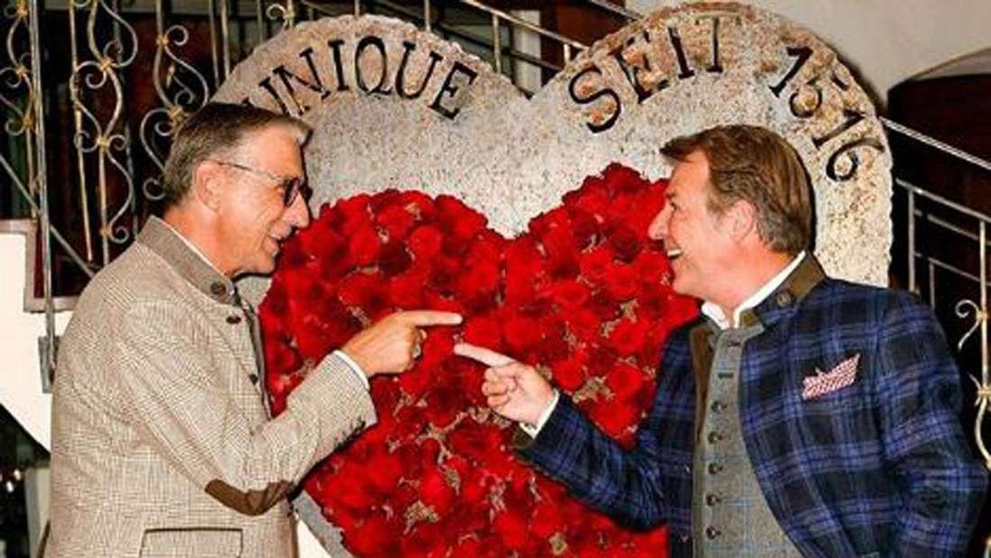 Patrick Lindner und Peter Schäfer zeigen gegenseitig auf sich und stehen vor einem roten Herz aus Rosen