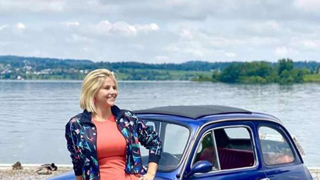 Beatrice Egli lehnt sich gegen ein Auto, im Hintergrund ein See