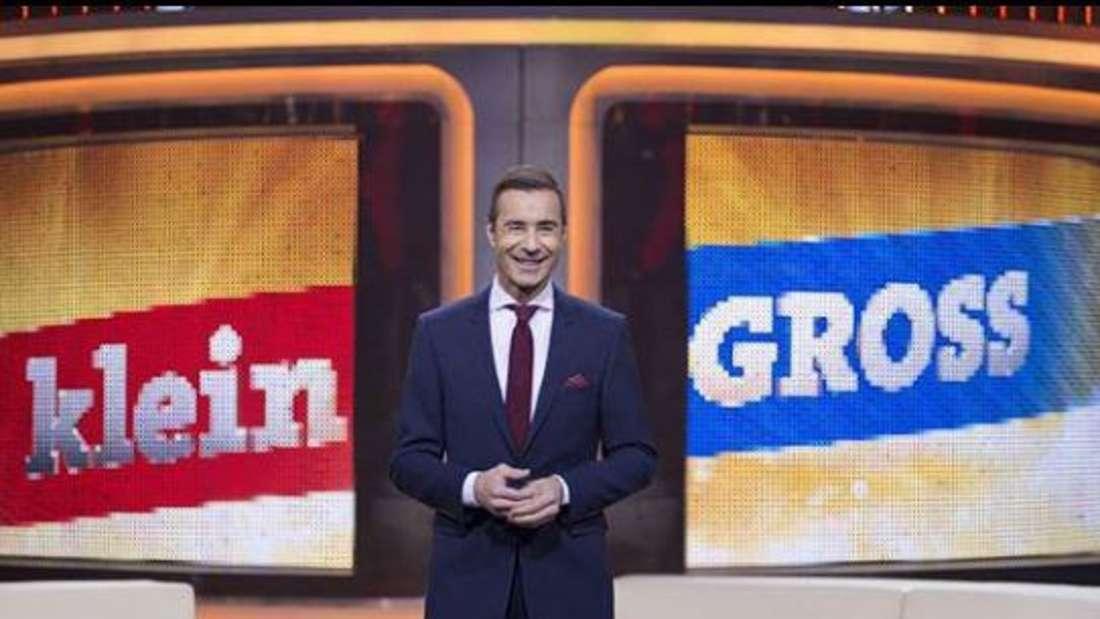 """Kai Pflaume im """"Klein gegen Groß""""-Studio, steht vor dem Logo und lächelt in die Kamera"""