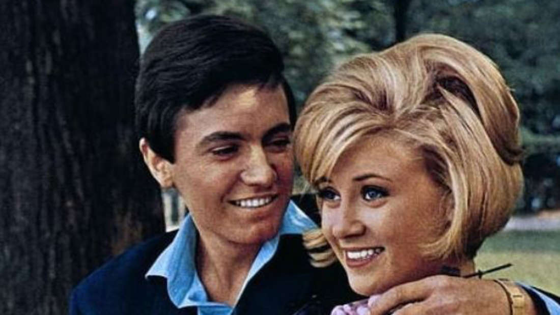 Gitte Haenning und Rex Gildo in einer Filmszene auf einer Bank im Park
