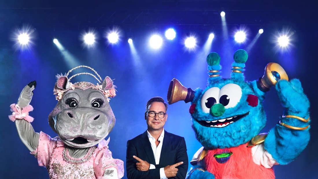 """""""The Masked Singer""""-Moderator Matthias Opdenhövel mit den Kostümen """"Das Nilpferd"""" und """"Das Alien""""."""
