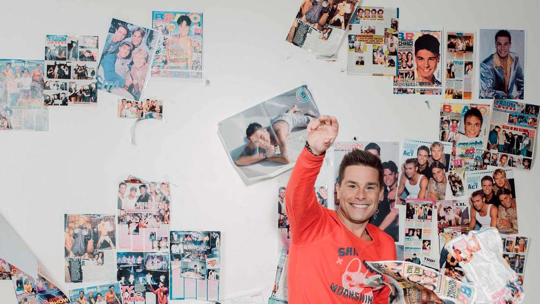 """Eloy de Jong hält eine Bravo in der Hand, an der Wand im Hintergrund hängen viele """"Caught in the Act"""" Poster"""