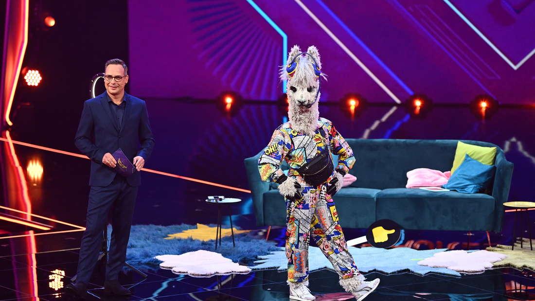 """Moderator Matthias Opdenhövel steht mit dem Alpaka auf der Bühne von """"The Masked Singer"""" und hört sich die Tipps des Rate-Teams an."""