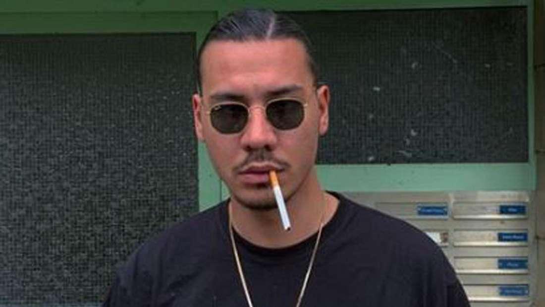Apache schaut in die Kamera und hat eine Zigarette im Mund