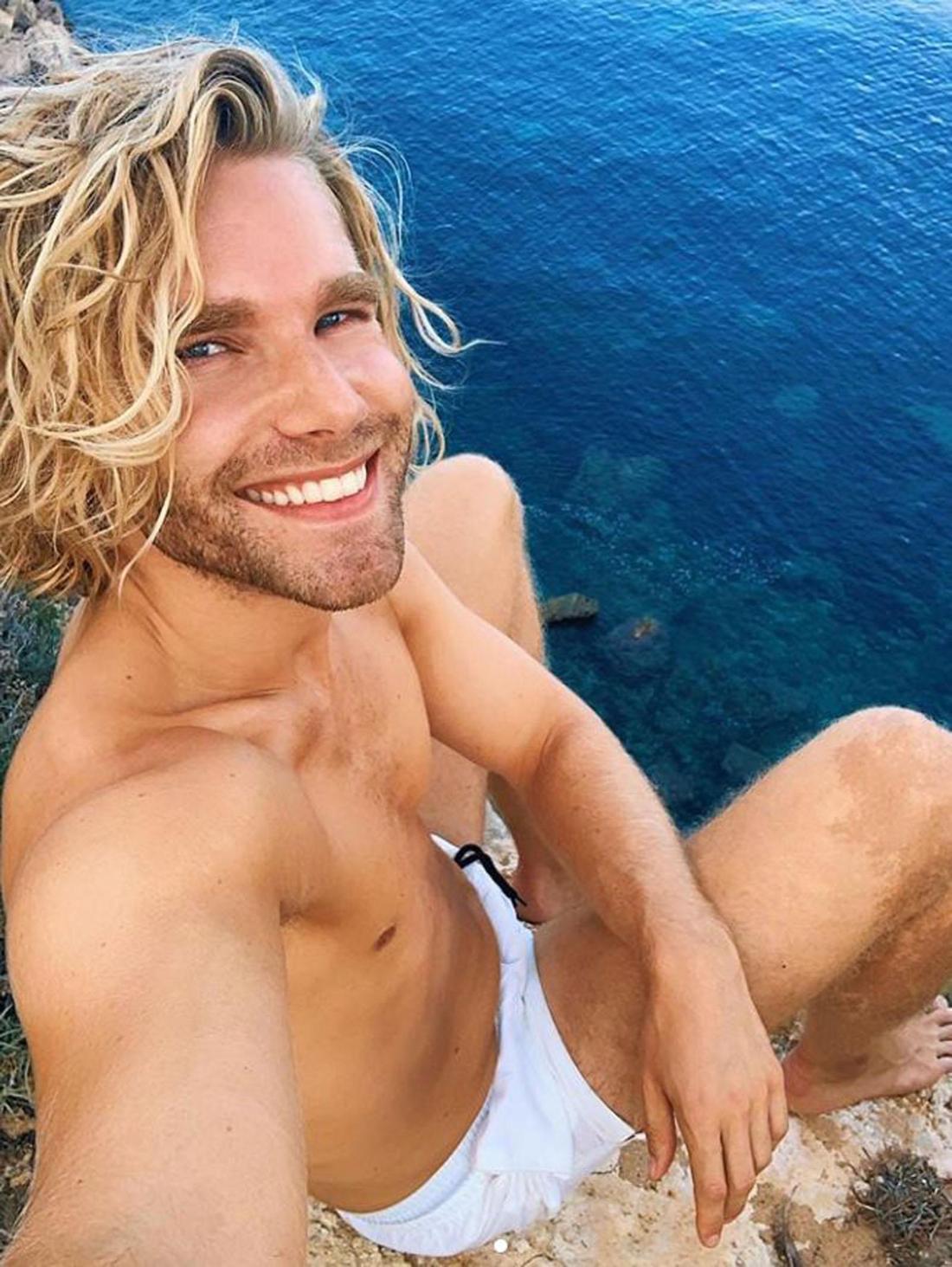 Martijn Stoffers sitz an einer Klippe, er lächelt und untem ihm ist Wasser