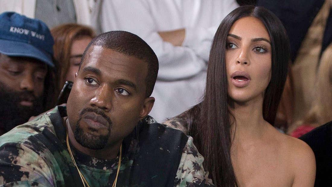 Kim Kardashian blickt erschrocken, Kanye West neben ihr blickt an der Kamera vorbei