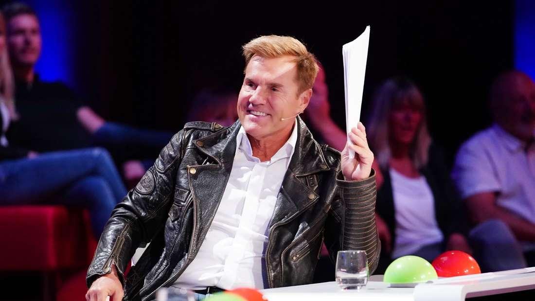 """Dieter Bohlen sitzt am """"Supertalent""""-Juroren-Pult. Er hält einen Papierstapel in der Hand, die er sich vor die Augen hält."""