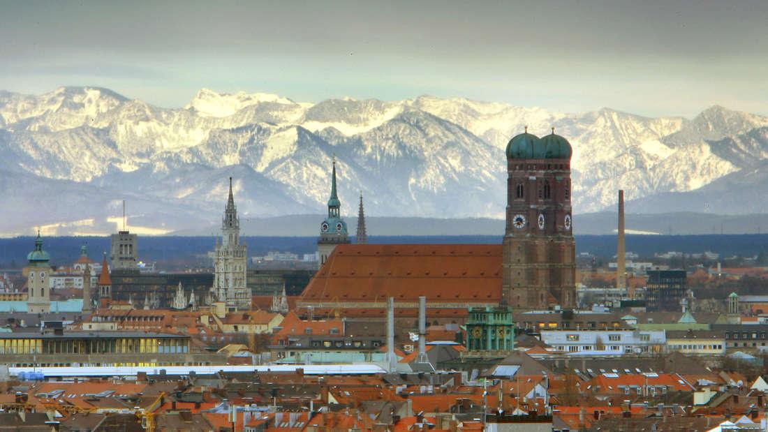 München: Die Frauenkirche steht vor den schneebedeckten Alpen.