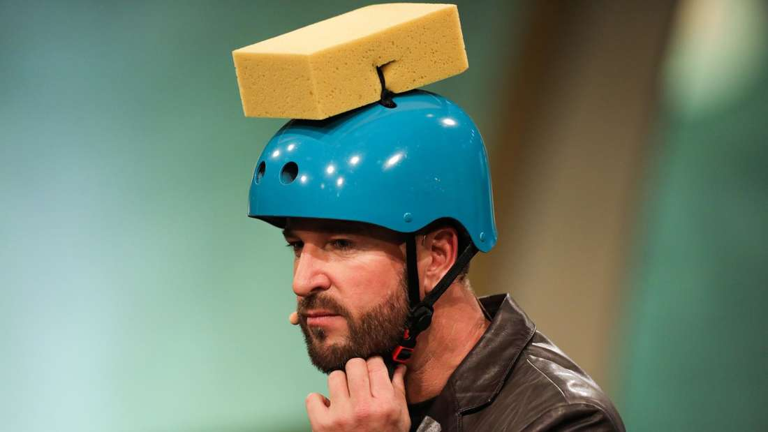 Michael Wendler in einer TV-Show mit einem Helm auf dem Kopf