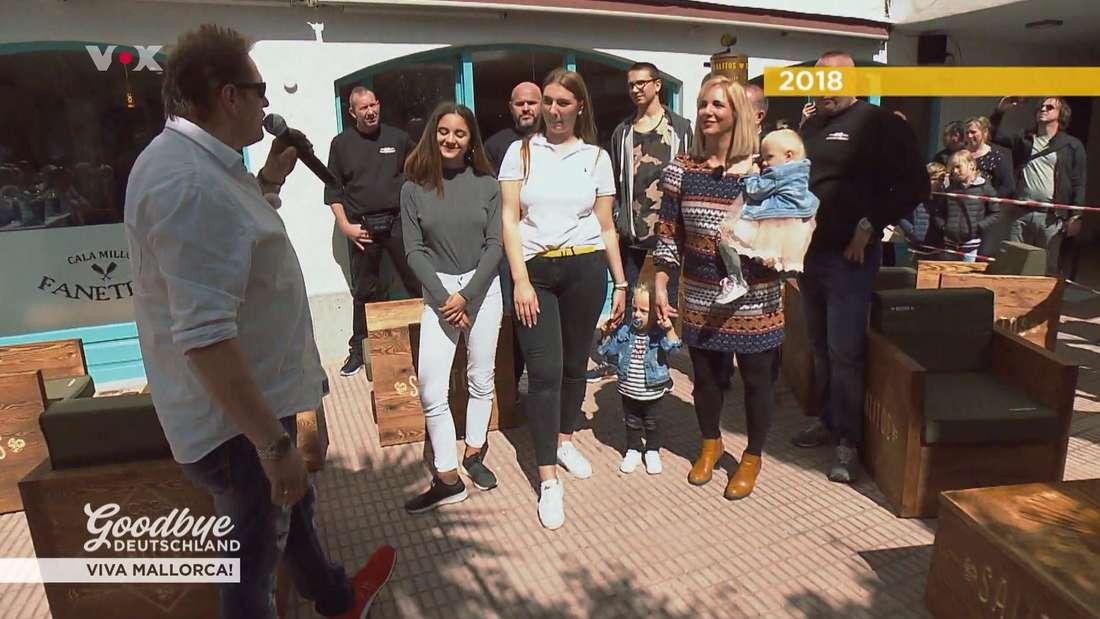 Jens Büchner links mit einem Mikrophon in der Hand, daneben steht Danni mit den fünf Kindern