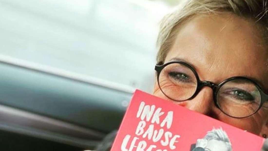 Inka Bause sitzt im Auto und hält ihr Album hoch