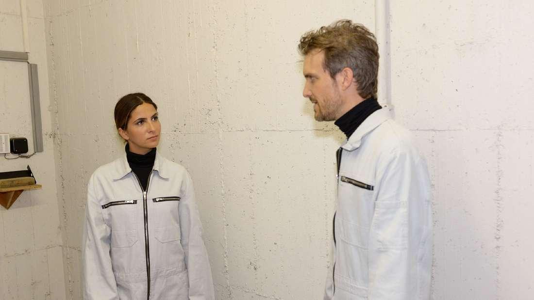 Felix und Laura tragen einen weißen Malerkittel und stehen sich gegenüber