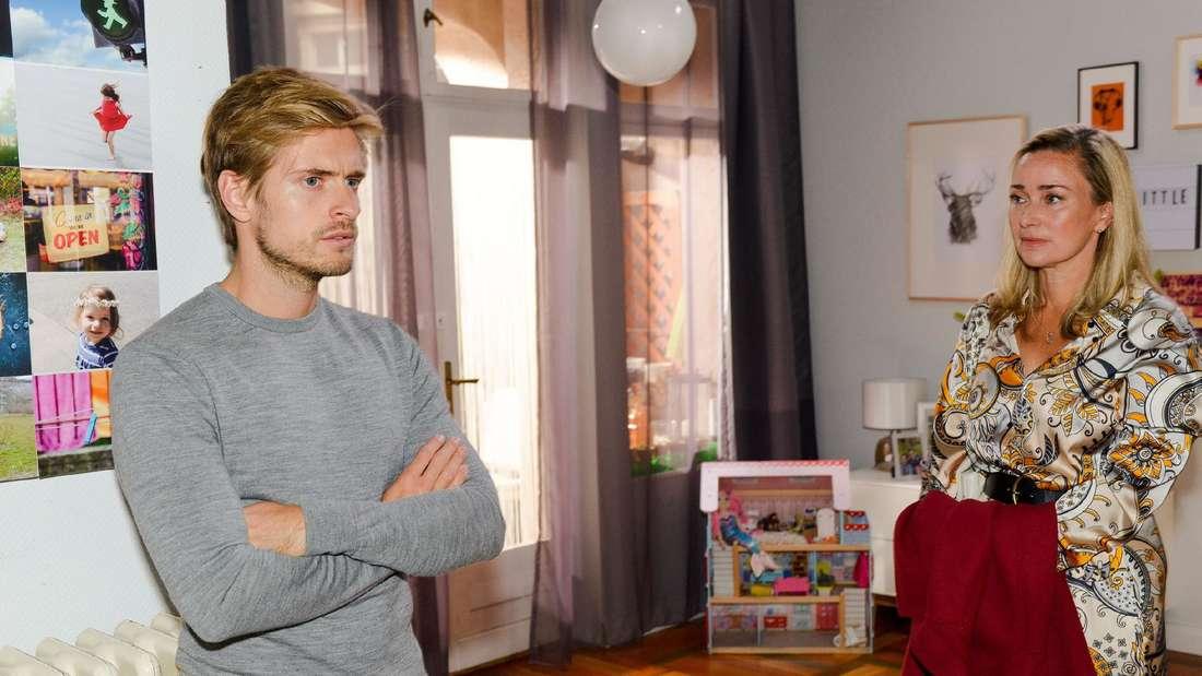 Patrizia und Philip stehen sich im Wohnzimmer gegenüber.