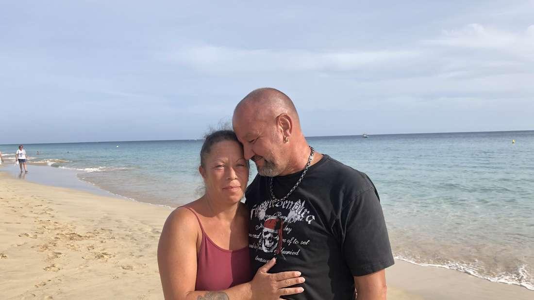 Uli und Karl Heinz halten sich im Arm und stehen an einem leeren Strand.