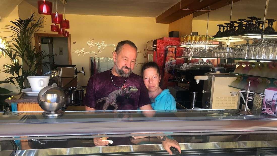 Uli und Karl-Heinz umarmen sich und stehen vor der Truhe mit ihren verschiedenen Eissorten