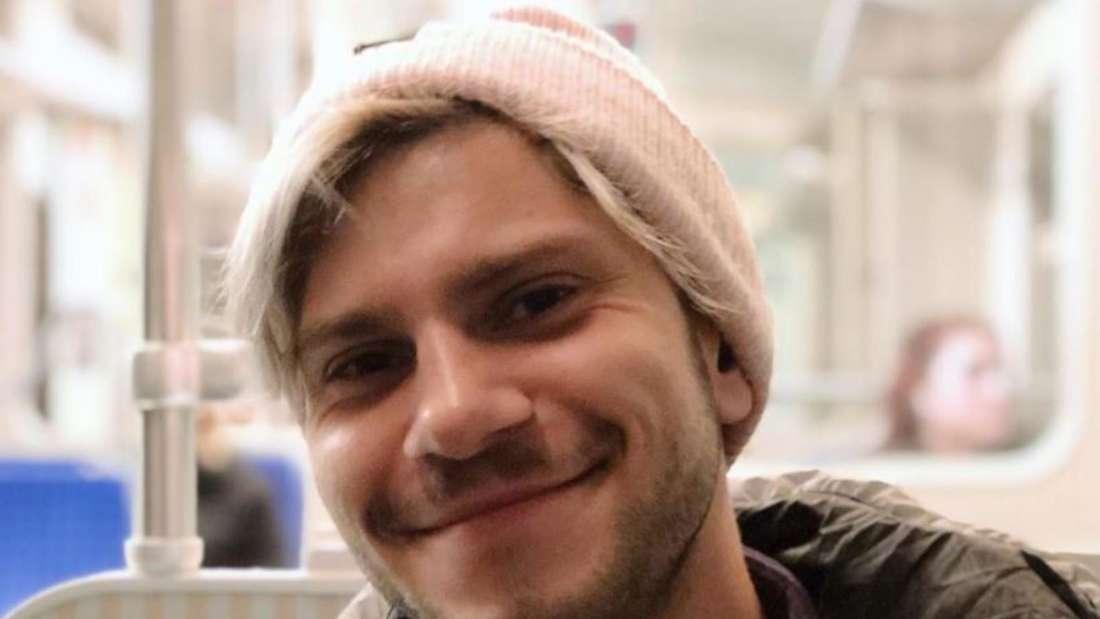 Julian Reim sitzt in der Bahn und lächelt