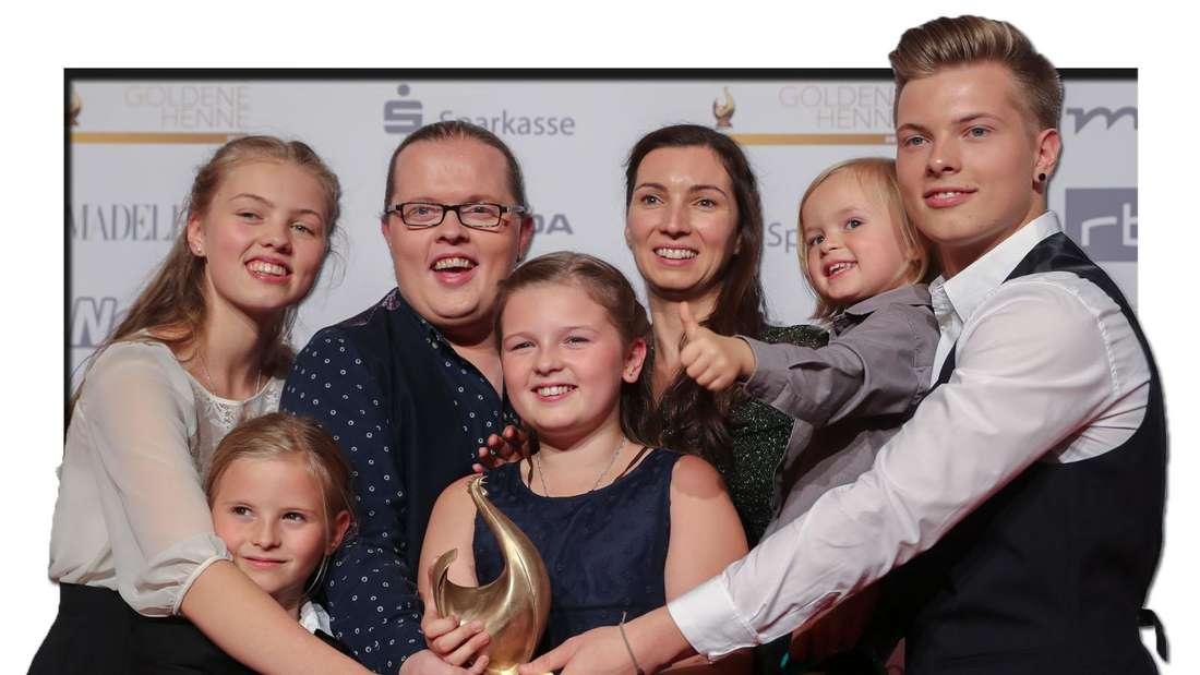 """Angelo Kelly jubelt mit seiner Familie Helen (l-r), Joseph, Emma, Mutter Kira, Wiliam und Gabriel nach dem Erhalt der """"Goldenen Henne"""" in Leipzig am 28.09.2018 (Fotomontage)"""