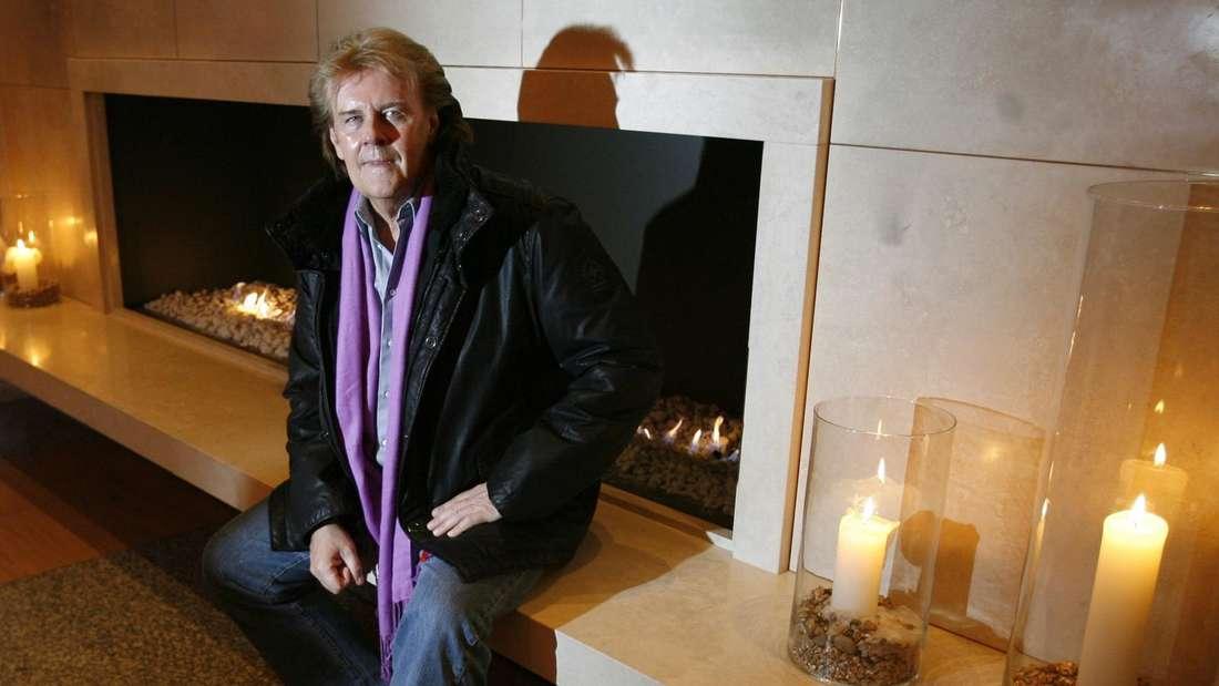 Howard Carpendale lehnt gegen ein Kamin und Kerzen sind um ihn herum