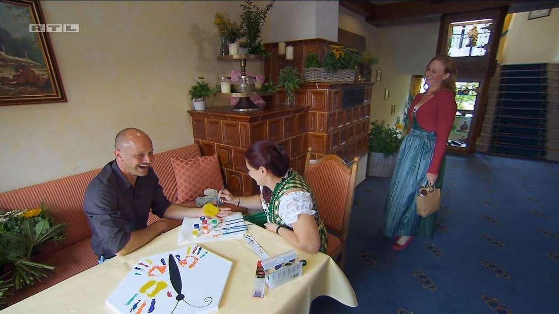 Gaby und Thomas sitzen an einem Tisch, Nicole läuft in den Raum hinein