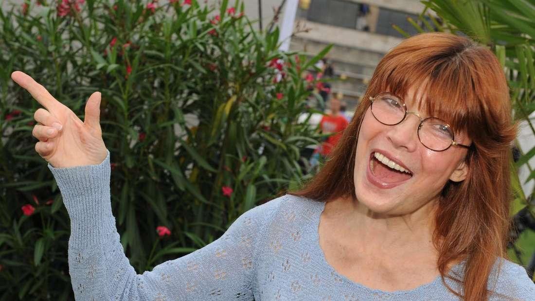 Katja Ebstein lacht und zeigt mit ihrem Finger zur Seite