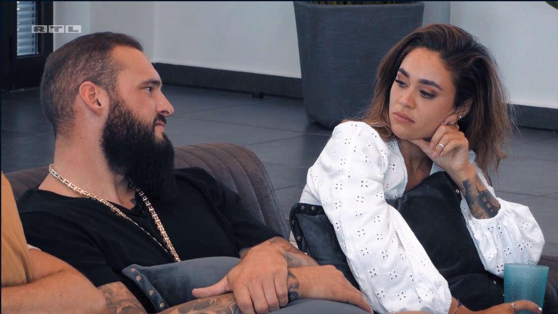 Melissa und Daniel sitzen auf einer Couch und schauen sich grimmig an