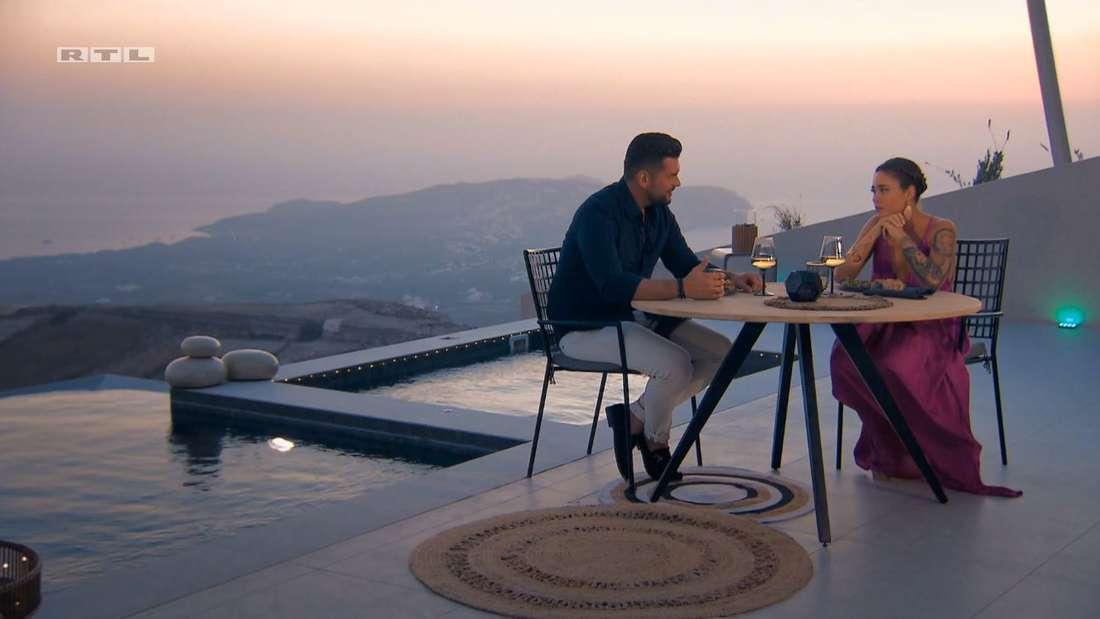 Melissa und Ioannis an einem Tisch, im Hintergrund das Meer, der Sonnenuntergang und Santorini