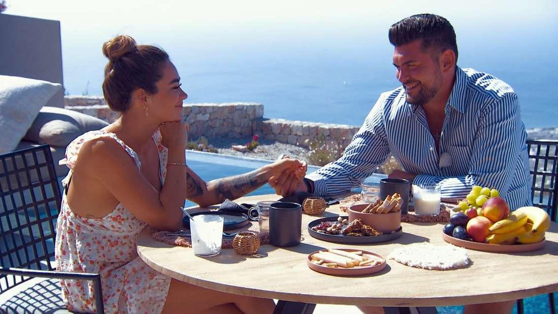 Melissa und Ioannis sitzen am Tisch mit Essen. Sie halten Händchen