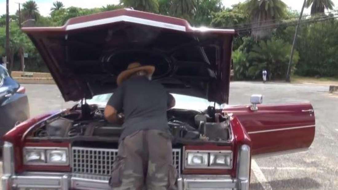 Konny Reimann hat die Motorhaube des roten Cadillacs geöffnet und sucht nach dem Fehler. Auf dem Boden steht ein Kanister