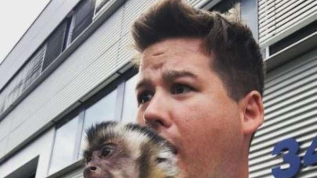Chris Tall macht ein Selfie mit einem Affen zusammen