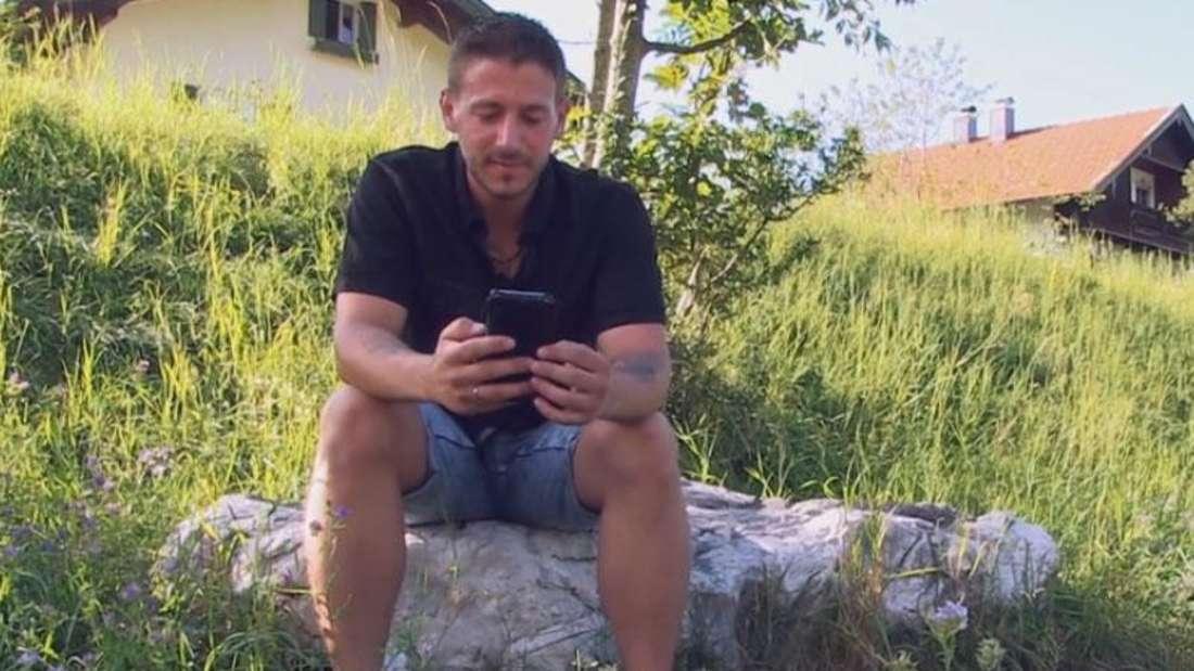 Hochzeit auf den ersten Blick: René sitzt auf einem Stein, macht einen Videocall mit Experte Thomas Ernst