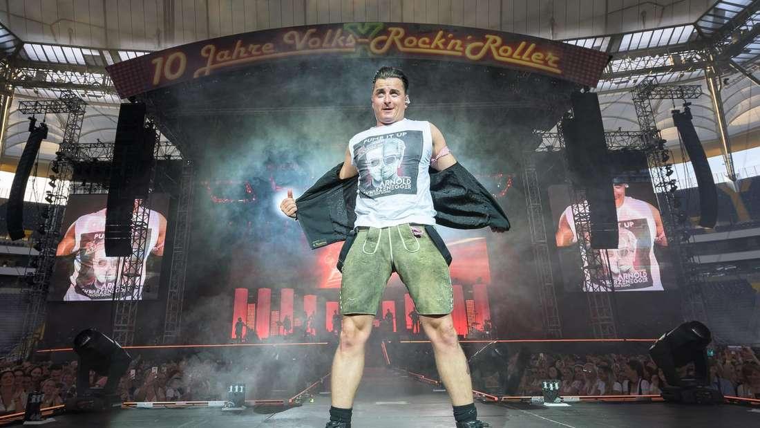 Andreas Gabalier steht auf der Bühne und zieht seine Jacke aus