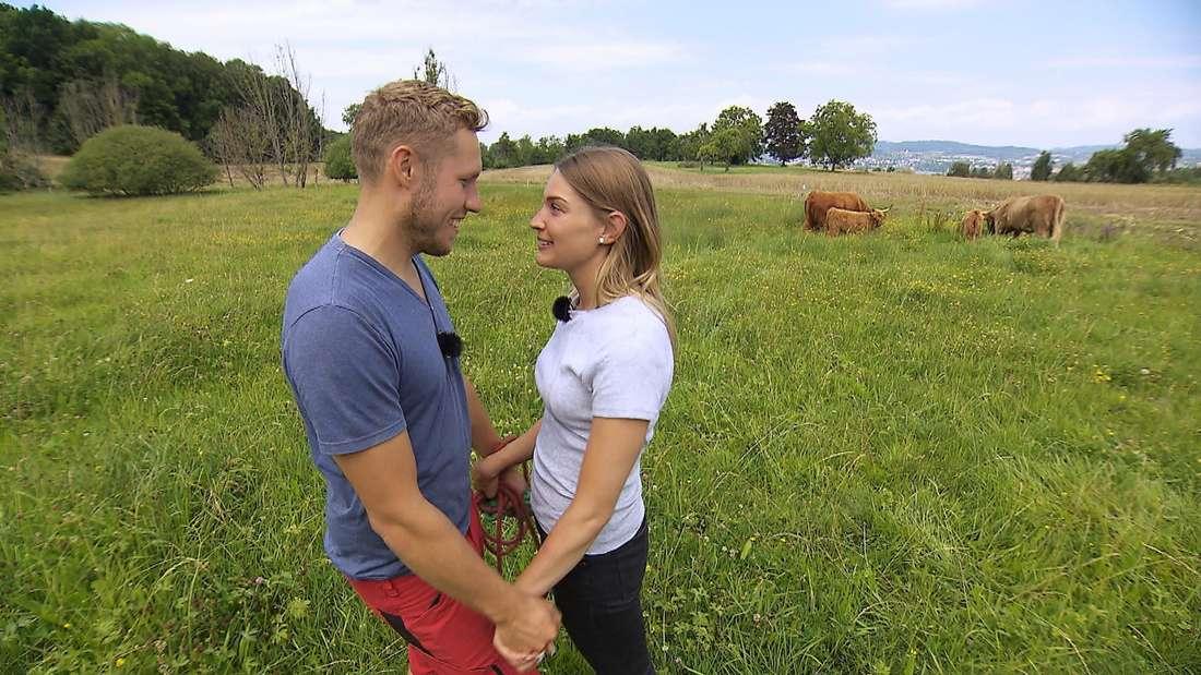 Julia und Patrick stehen auf der Kuhweide und blicken sich in die Augen.