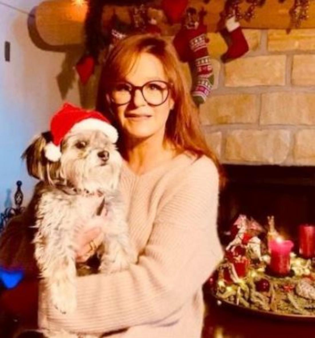Andrea Berg steht vor einem Kamin mit ihrem Hund auf dem Arm, der eine Weihnachtsmütze trägt